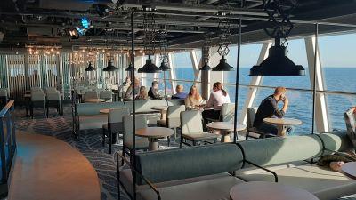Folk sitter i pub i båt och tittar ut på havet.