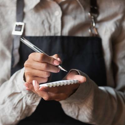 En servitris håller i ett block och en penna och skriver ner en beställning.