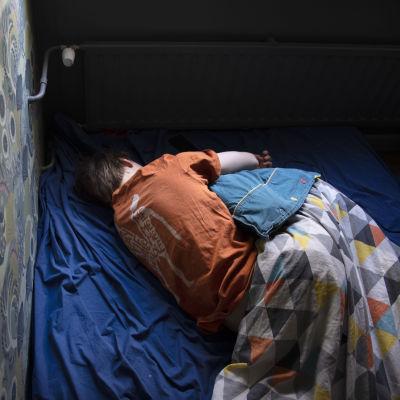 En ung människa ligger i sin säng.