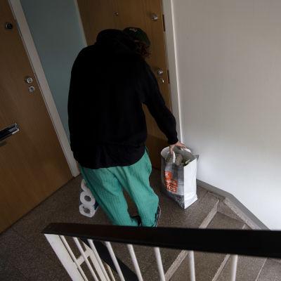 MIes jättää kauppakassin oven ulkopuolelle kerrostalon rappukäytävässä.