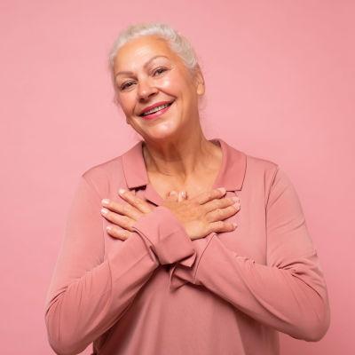 Leende äldre kvinna framför rosa bakgrund