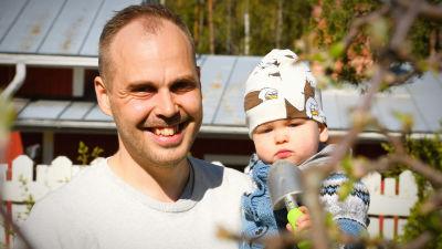 Martin Norrgård med sonen i famnen i vårsolen hemma på gården
