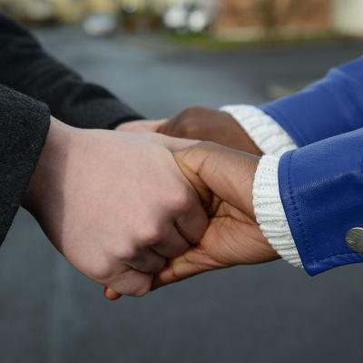 Två unga människor håller hand.
