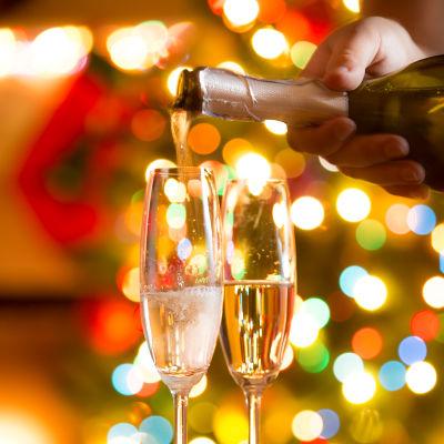 Hand häller mousserande vin i glas