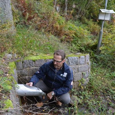 Olav Granström sitter vid ett vattenrör