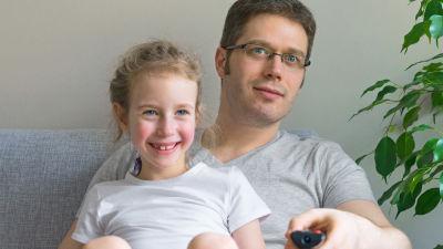 Pappa och dotter sitter på soffan och tittar på tv.
