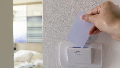 En person sätter in ett nyckelkort i en apparat på väggen i ett hotellrum.
