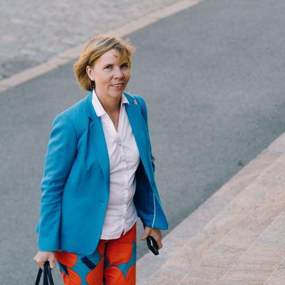 Anna Maja Henriksson i blå kavaj och storblommiga byxor. Hon går upp för en trappa.