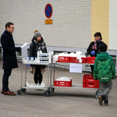 Lapsia hakemassa kouluruokaa Heinolassa maaliskuussa 2020