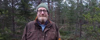 En man står i en skog.