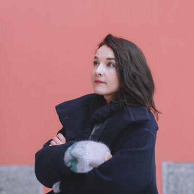Artisti Iisa vaaleanpunaisen talon edessä seisomassa