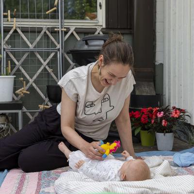 Äiti leikkii viltillä makaavan vauvan kanssa