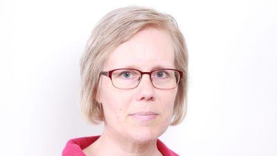 En kvinna i ljust hår och glasögon ser in i kameran.