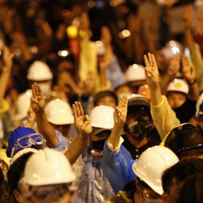 Kypäräpäisiä mielenosoittajia kolme sormea pystyssä