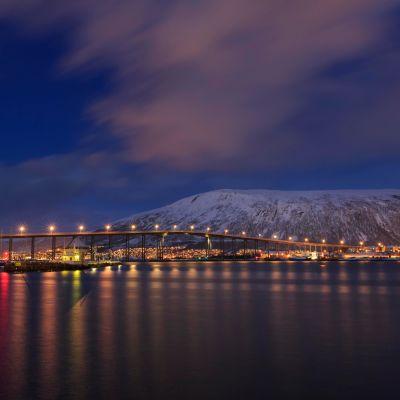 Hämärässä otettu kuva Tromssan kaupungista. Etualalla vettä.
