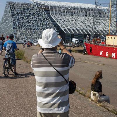 ihmisiä on tullut katsomaan ja ottamaan kuvia majakkalaiva Kemistä Kotkan kantasatamaan, taustalla merikeskus Vellamo