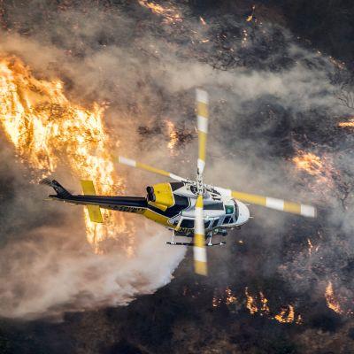 En brandhelikopter flyger ovanför branden i stadsdelen Bel-Air, Los Angeles på onsdag morgon, lokal tid.