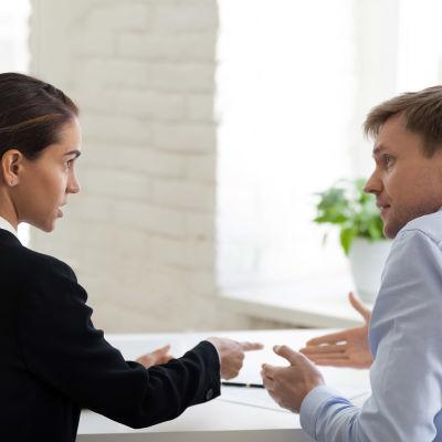 Kvinna i mörk kavaj och man i ljus skjorta tittar irriterat på varandra