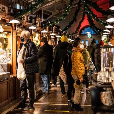Folk på juluppköp i Gamla saluhallen i Helsingfors den 23 december.