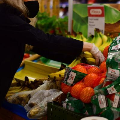Ett butiksbiträde ordnar bananer och apelsiner med plasthandskar på.