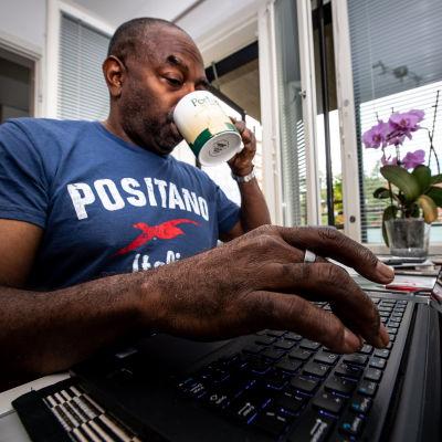Mies työskentelee kannettavan tietokoneen kanssa kotona.