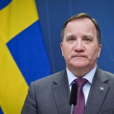 En allvarlig man i övre medelåldern klädd i kostym ser in i kameran. Snett bakom honom finns Sveriges flagga.