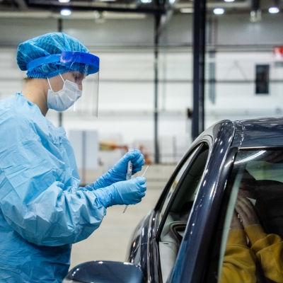 En sjukskötare klädd i blå skyddsutrustning håller upp en pipett framför en bilförare som ska testas för covid-19.