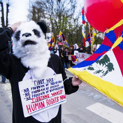 Under en demonstration håller en person i pandakostym en tibetansk flagga i handen.