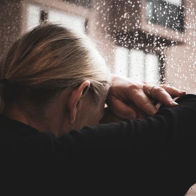 nainen nojaa päätänsä sateiseen ikkunaan.