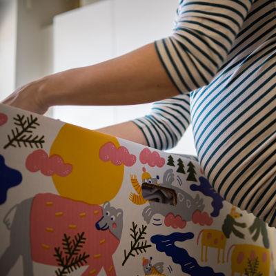 En mamma med gravidmage inspekterar innehållet i en en babylåda.