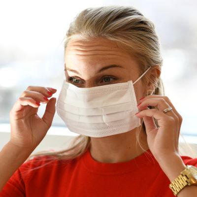 Eva Brunell sätter på sig ett munskydd.
