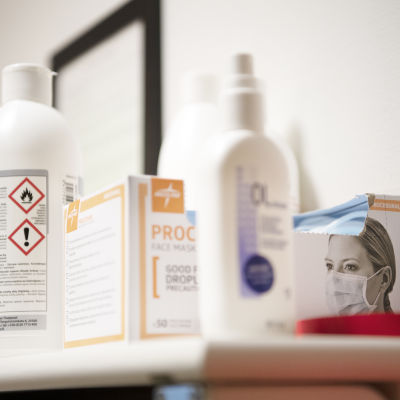 Ansiktsmaskar och desinfektionsmedel i ett patientrum på ett sjukhus.