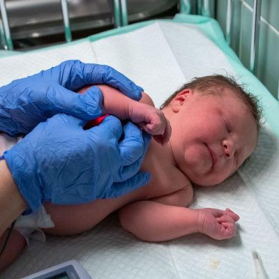 Nyfödda Ronja ligger på skötbordet. Hon har ögonen fast. Mervis har blåa engångshandskar på händerna. Hon pysslar om Ronja.