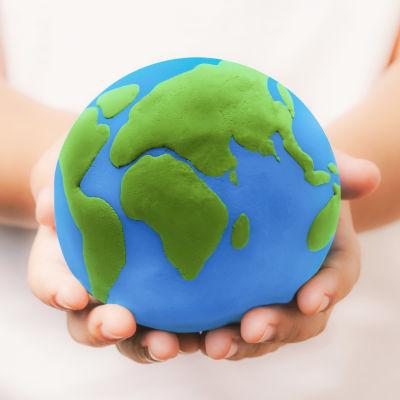 ihminen pitää käsissään maapalloa