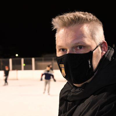 En man med svart munskydd vid en ishockeyrink utomhus.