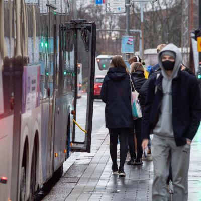 Människor kliver på en buss i Helsingfors. Mot kameran går en man med munskydd.