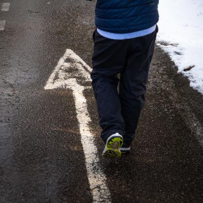 Lapsi kävelee tiellä nuoli merkin päältä.