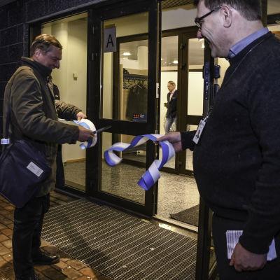 Kommunstyrelsens ordförande Kaj Lindqvist klipper av blåvita bandet och personalchef Jan Rosenström håller i