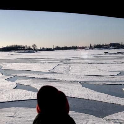 Henkilö katsoo jäätynyttä Suomenlahtea lautalla.