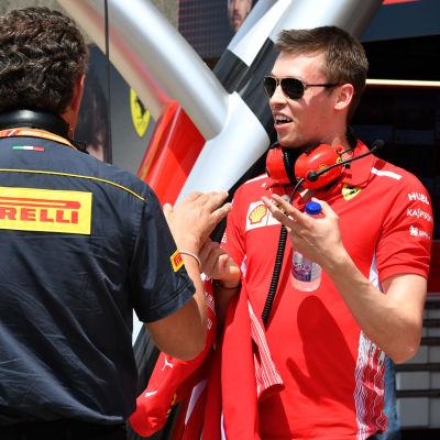 F1-föraren Daniil Kvjat i samspråk med mekaniker.