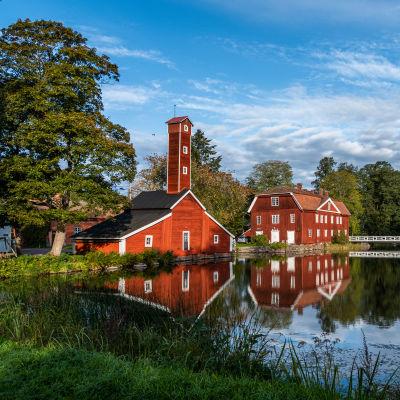 Två gamla röda hus vid en spegelblank sjö på en klar dag