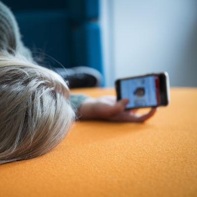 Tyttö makaa sohvalla ja katsoo kännykän näyttöä