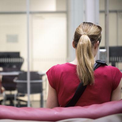 Asiakas Terveysaseman odotusaulassa. Ihmisiä terveyskeskuksessa odottamassa lääkärille pääsyä.