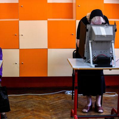Ihmisiä äänestyskoneiden takana värikkään kaapiston edessä