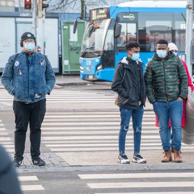 Tre män står och väntar på att få gå över vägen vid ett övergångsställe. Alla tre har munskydd.