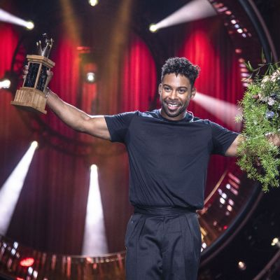 John Lundvik håller upp trofén och en blombukett efter att ha vunnit Melodifestivalen.