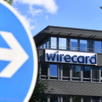 Wirecard-yhtiön nimikyltti rakennuksen seinässä. Etualalla liikennemerkki.