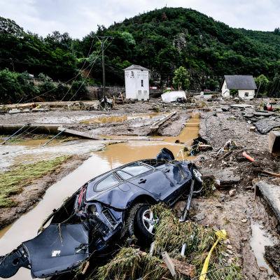 Flera rasade hus i tyska Schuld och en bild som ligger på sidan i vatten och lera.