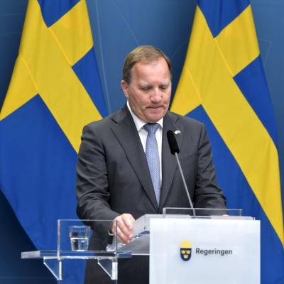 Stefan Löfven framför två svenska flaggor.