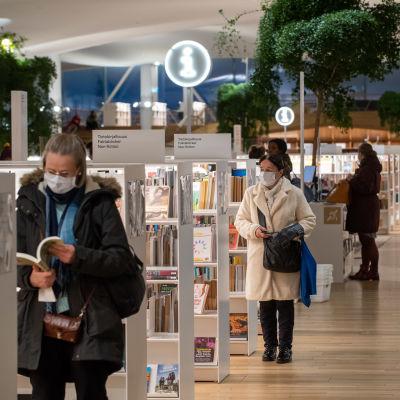 I bilden syns en mängd vita bokhyllor som är fyllda av böcker. Människor står i utrymmet med böcker i händerna. De bär munskydd.